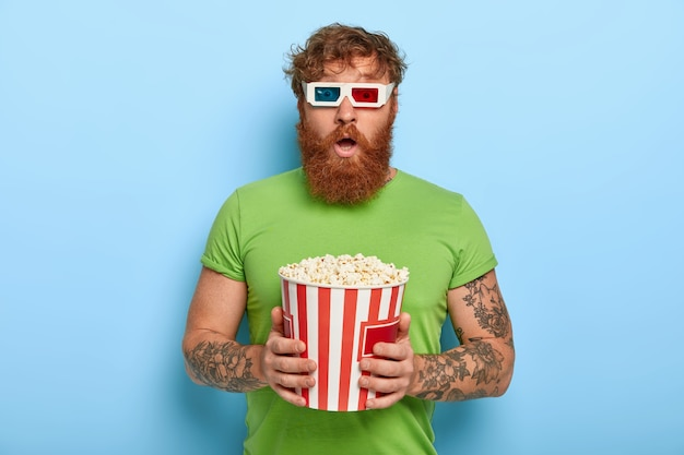 People and pastime concept. scared bearded ginger man watches film which get his reaction