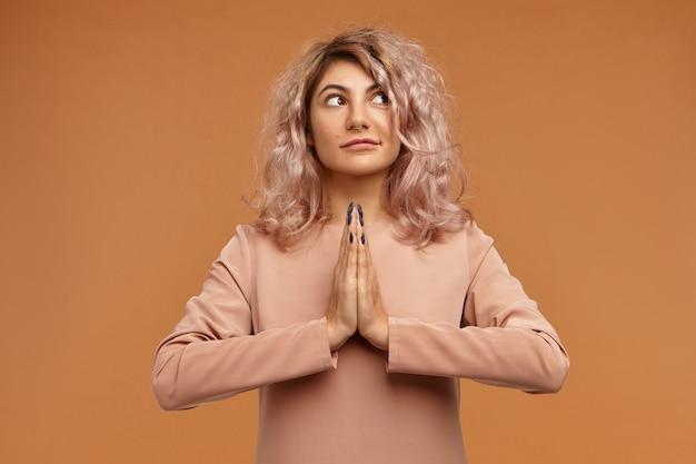 人、平和、瞑想、そして禅の概念。鼻ピアスとナマステで手をつないで、瞑想している巻き毛を持つファッショナブルな若い女性の写真