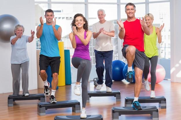 체육관에서 단계 에어로빅 운동을 수행하는 사람들