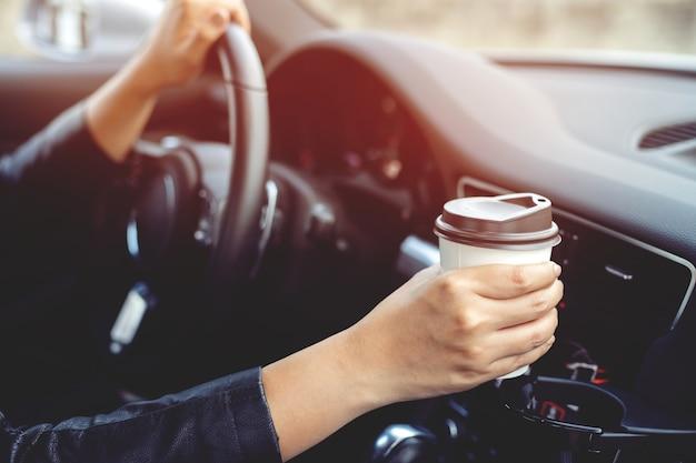 朝、車の中で熱い握り手の紙コップコーヒーを飲んでいる人は、運転中は元気になります。輸送と車両のコンセプト。テキスト用の空のコピースペース。
