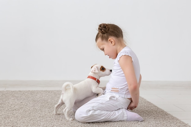 人、ペット、動物のコンセプト-白い背景の上に床に座って、子犬ジャックラッセルテリアを保持している少女。