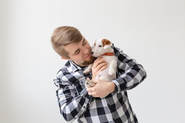 人、ペット、動物の概念-白でジャックラッセルテリアの子犬を保持しているハンサムな男