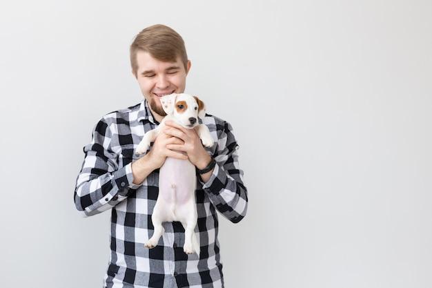 人、ペット、動物の概念-白い壁にジャックラッセルテリアの子犬を保持している若い男