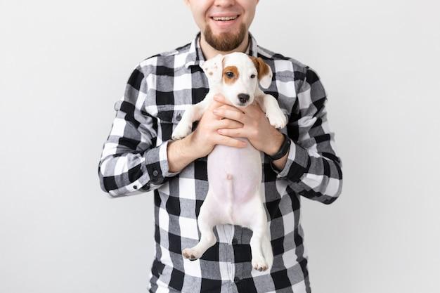 人、ペット、犬の概念-白い背景の上の面白い子犬を抱き締める男のクローズアップ
