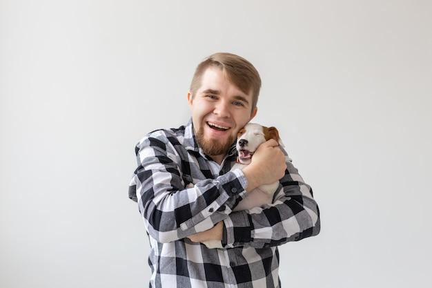人、ペット、犬のコンセプト-白い背景に面白い子犬を抱き締める若い男