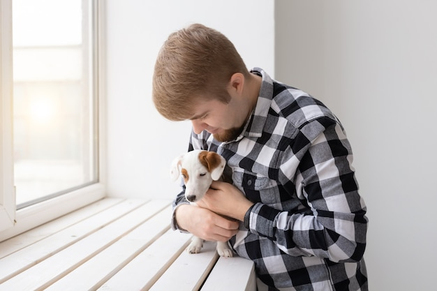 People, pets and animals concept - young man hugging puppy near window on white background