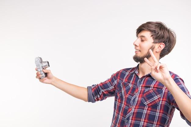 사람, 사진 작가 및 제스처 개념-흰색 배경에 렌즈를 통해 찾고 구식 카메라를 사용하는 사람