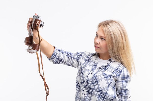 Люди, фотограф и концепция жестов - женщина, использующая старомодную камеру, смотрящую через объектив на белой поверхности