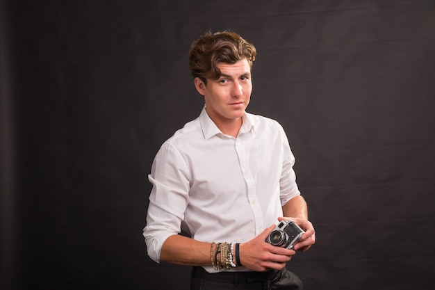 People, photographer and vintage concept - man searching for an interesting subject for his photo holding a vintage camera on brown surface
