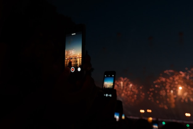 People photographing fireworks celebration with phone. focus is on smart phone.