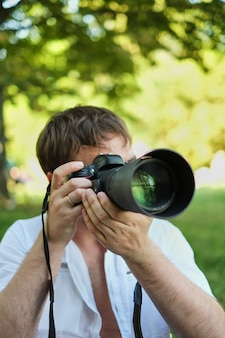 People photography technology leisure and lifestyle hipster man holding digital camera with big lens