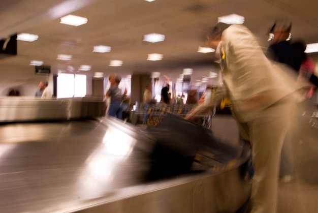 People picking up luggage from conveyor belt