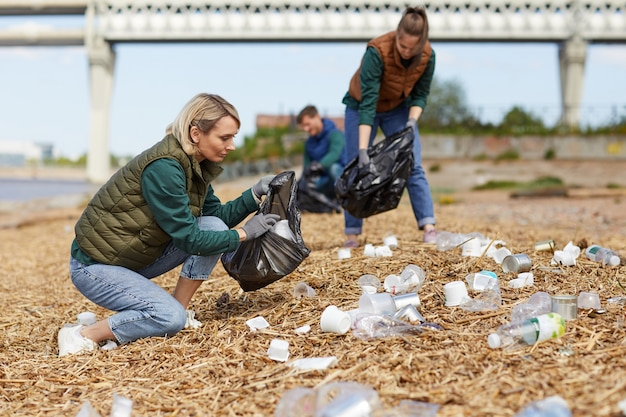 Люди собирают мусор в мешках у реки на улице