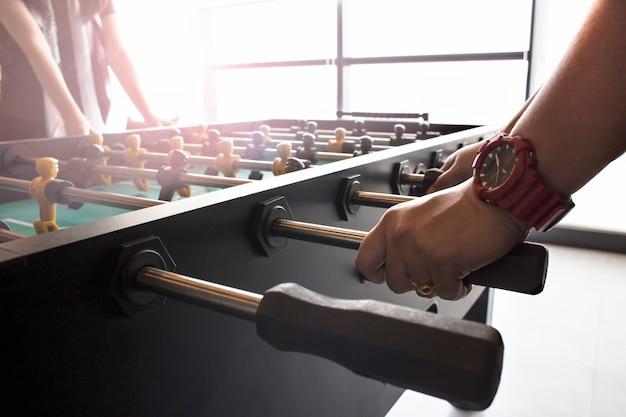 People playing enjoying foosball table soccer game black and yellow players