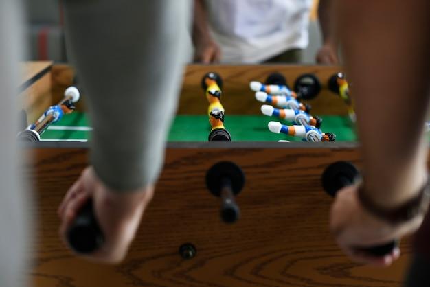 La gente che gioca godendo di svago di ricreazione del gioco di calcio della tabella di calcio-balilla