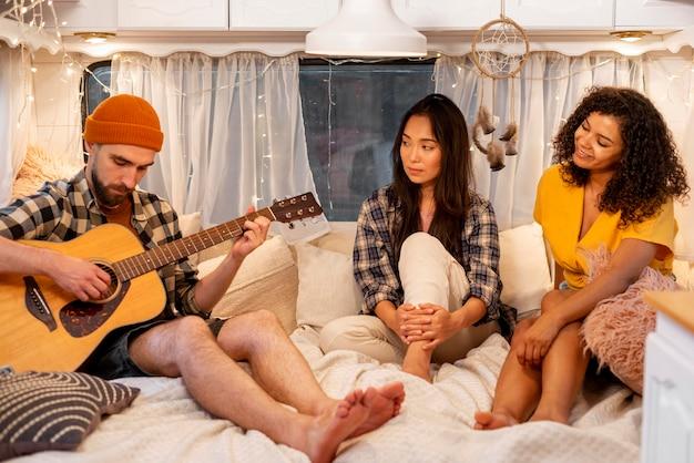 Люди играют на гитаре в концепции приключенческой поездки в фургоне