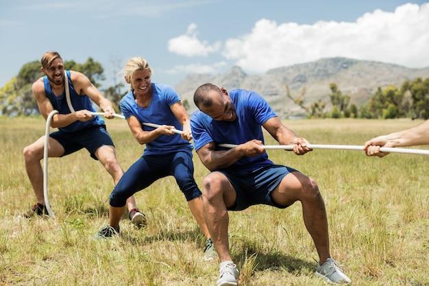 Люди играют в перетягивание каната во время тренировки с препятствиями