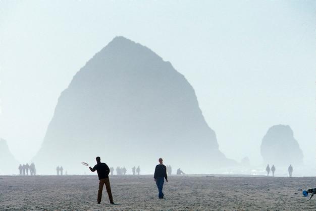Люди, играющие с собакой в cannon beach oregon
