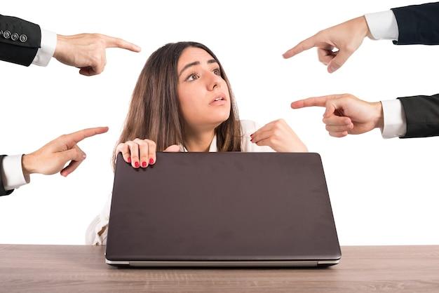 Люди указывают на женщину, спрятанную за компьютером