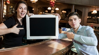 People pointing at blackboard in cafe