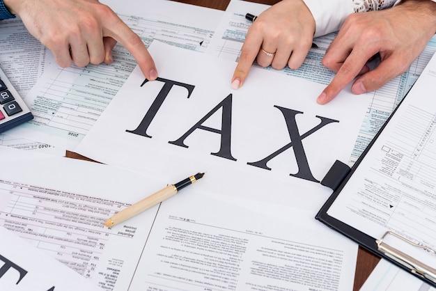 Люди, указывающие слово налог на листе бумаги