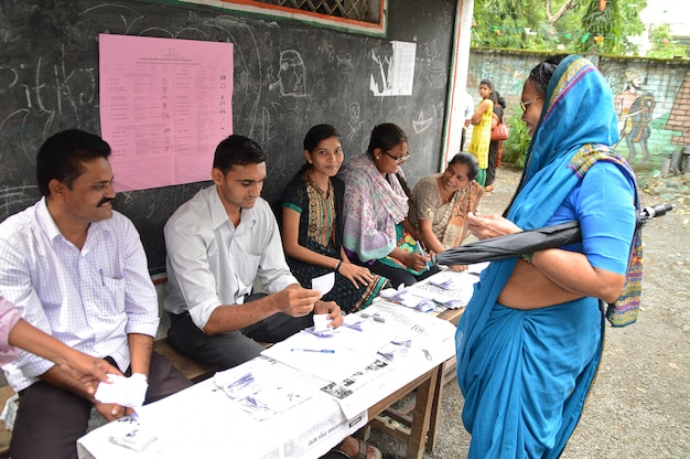 People and polling officers looks for a voters name in the list and complete the process of voting during election