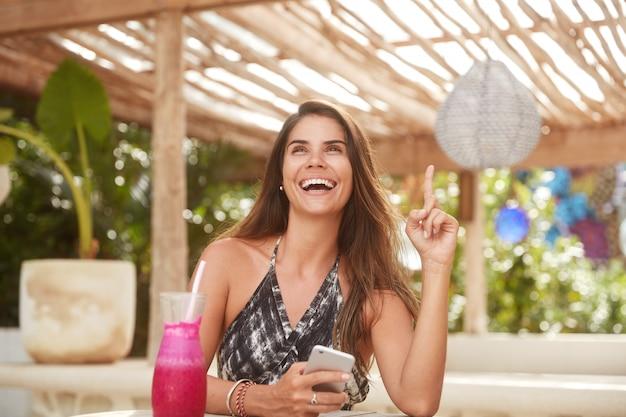 人、前向きな感情、テクノロジーのコンセプト。大喜びの女性はオンライン通信に最新の携帯電話を使用し、友人を祝福することを思い出しながら人差し指を上げ、歩道バーで休む