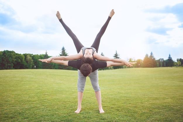 Люди практикуют акро-йогу на открытом воздухе здоровый образ жизни