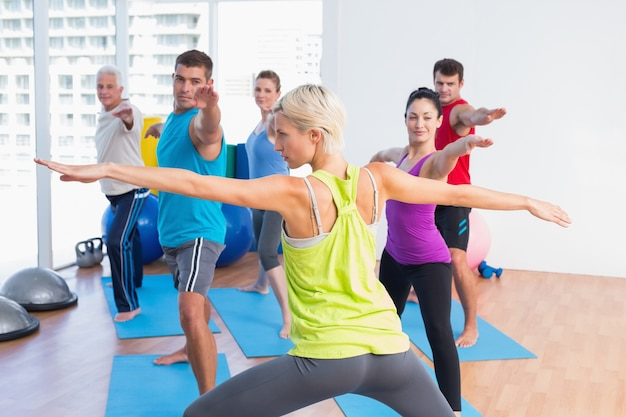 People practicing warrior pose in fitness club
