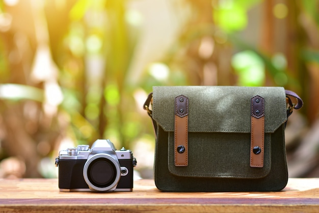 People prepare camera and bag on wood table vintage before use take photo