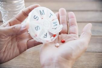 人々はピルボックスで毎日の薬のタブレットを準備します。
