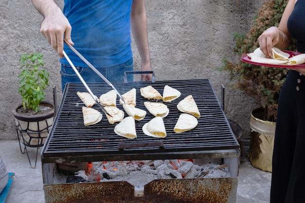 炭火焼きでケサディーヤを作る人