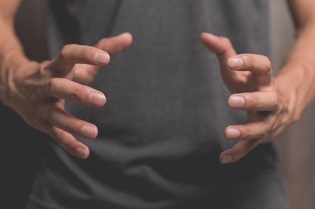 両手を広げて物を持つふりをする人