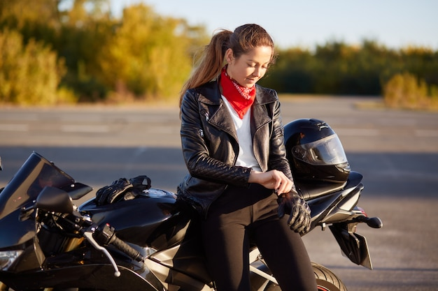 People, protection and driving concept. pretty woman biker puts on protective gloves, helmet, prepares for driving on motorbike, poses against nature blurred