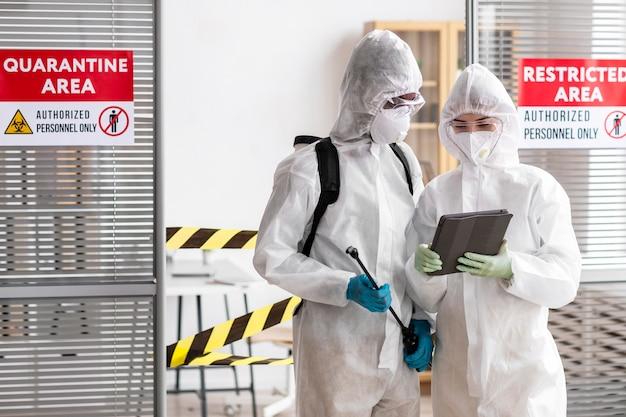 Persone in equipaggiamento protettivo che disinfettano un'area pericolosa