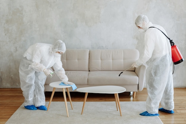 People in a protective suit with a disinfectant sprayer to disinfect household and furniture. the concept of a pandemic disinfection of coronavirus or covid-19. disinfection of rooms, houses
