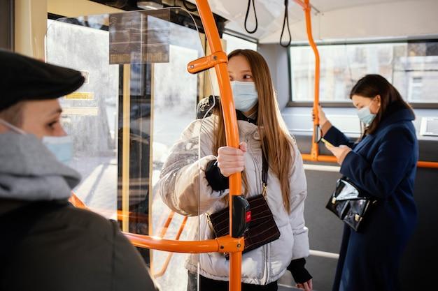 Persone nel trasporto pubblico che indossano la maschera