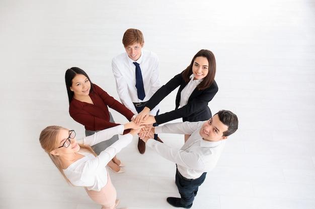 실내에서 손을 모으는 사람들. unity 개념