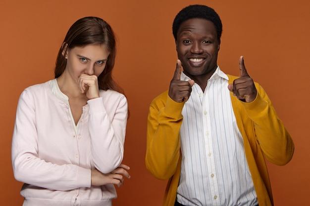 人、人種、民族。幸せな興奮した若いアフロアメリカ人の男は嬉しそうに笑って、前指を指して、彼女の口に拳を持って、笑ってかわいい長い髪のヨーロッパの女の子