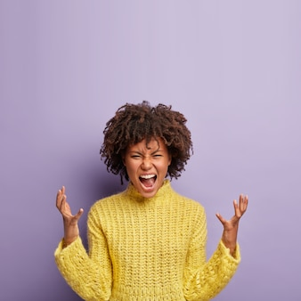 People, rage, irritation concept. emotional outraged crazy woman gestures angrily, raises hands, shouts madly on husband, expresses negative emotions, wears yellow clothes, isolated on purple wall.