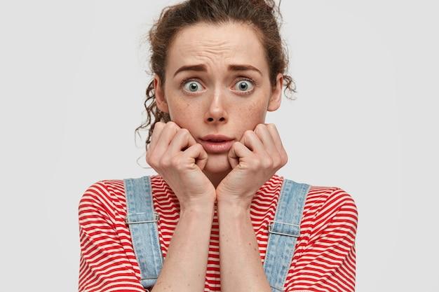 Persone e concetto di reazione. stordita bella donna lentigginosa tiene le mani sotto il mento, guarda con gli occhi verdi, riceve notizie scioccanti, isolato su un muro bianco, indossa una maglietta rossa a strisce