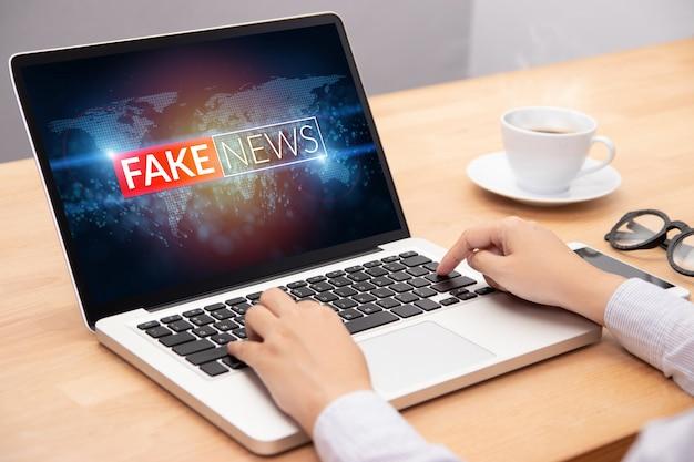 ラップトップを介してインターネットコンテンツで偽のニュースやhoaxを読んでいる人