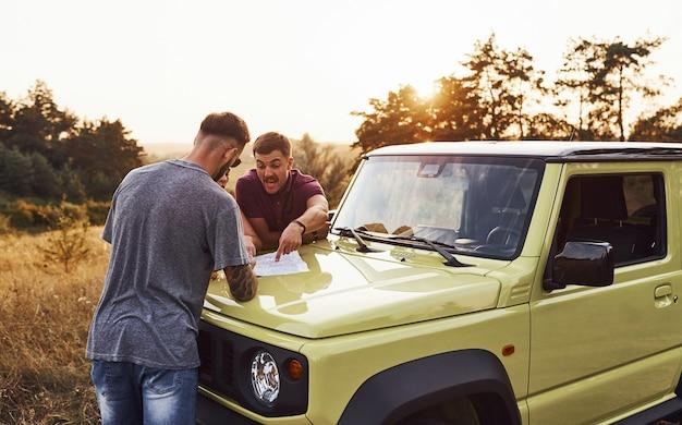 自動車のボンネットの上に横たわっている地図を読んでいる人々