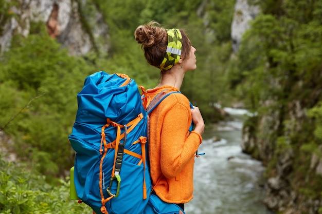 人、レクリエーション、旅行のコンセプト。思いやりのある女性の横向きのショットはリュックサックを運び、夏の遠征をしています