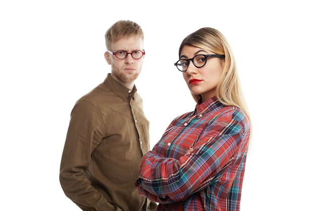 人、人間関係、仕事、キャリア、協力、チームワークの概念。真面目なルックスを持って、腕を組んでポーズをとっている眼鏡をかけた無精ひげを生やした若い男性と金髪の女性の同僚の肖像画