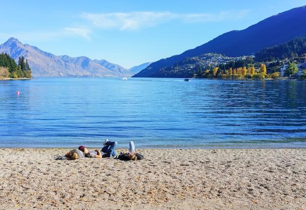 晴れた日にワカティプ湖のビーチでリラックスする人々、クイーンズタウン、ニュージーランドの南島