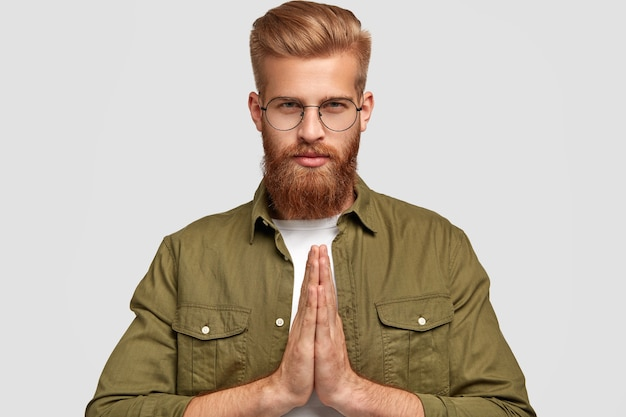 People and religion concept. serious unshaven young hipster keeps hands in praying gesture