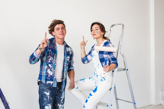 People, repair and relationship concept - young funny couple doing renovation in new apartment.