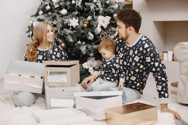 クリスマスのために修理する人々。子供と遊ぶ人。家族はお祭りの部屋で休んでいます。