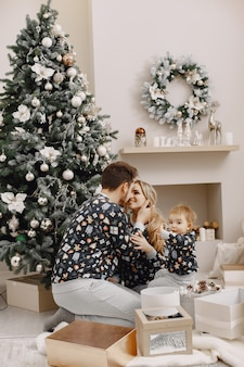 크리스마스를 위해 수리하는 사람들. 아이 함께 노는 사람들. 가족은 축제 방에서 쉬고 있습니다.